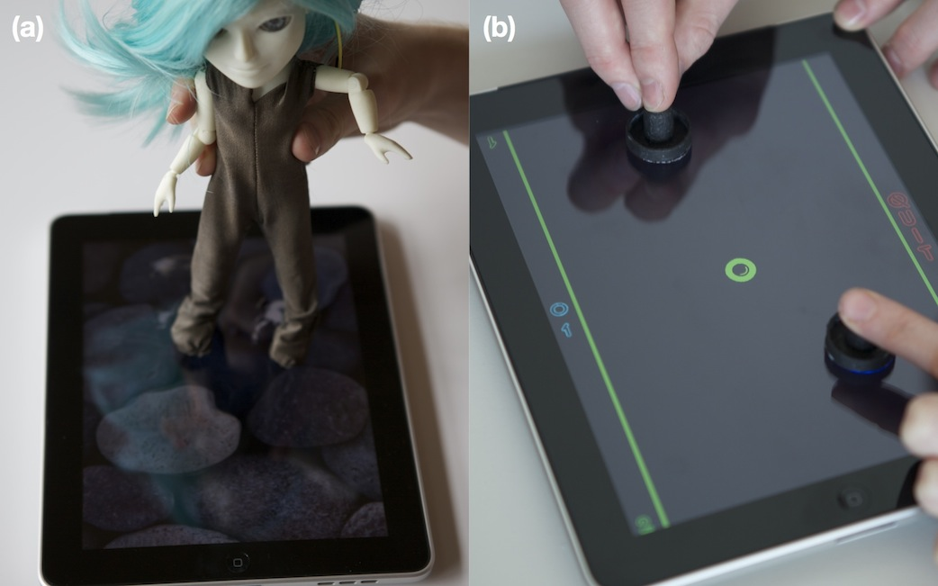 a) Makie fitted with clothes made from conductive cloth interacting with iPad; b) Physical game object produced from conductive material that acts as an object within a virtual game.